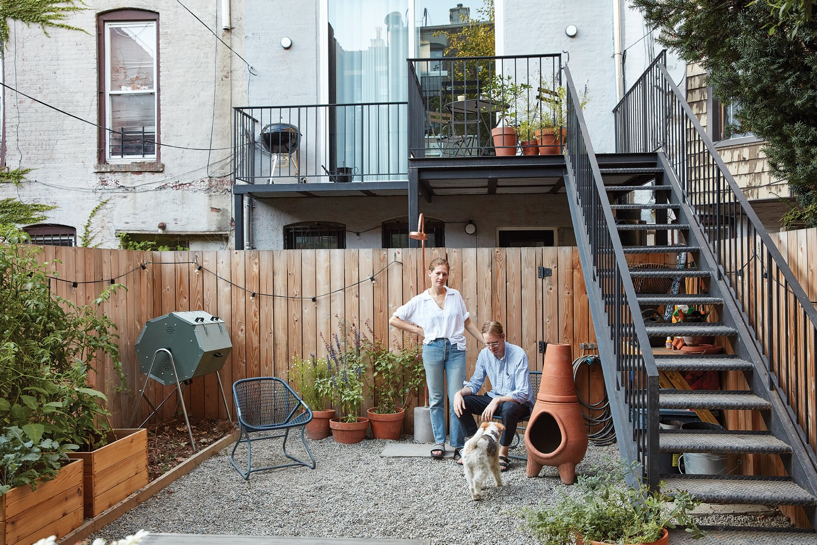 Outdoor, Small Patio, Porch, Deck, Stone Patio, Porch, Deck, Gardens, and Raised Planters It feeds their backyard garden, which also features permeable paving rocks, a composting  bin, and a surrounding fence made  of knotty Western red cedar.  Photo 15 of 16 in Forever Changes