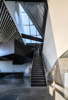 The faceted corrugated metal ceiling opens up over the staircase, soaring to a height of 32 feet above the ground floor. Like much of the metalwork, the steel staircase and railing were fabricated by Tutto Ferro.