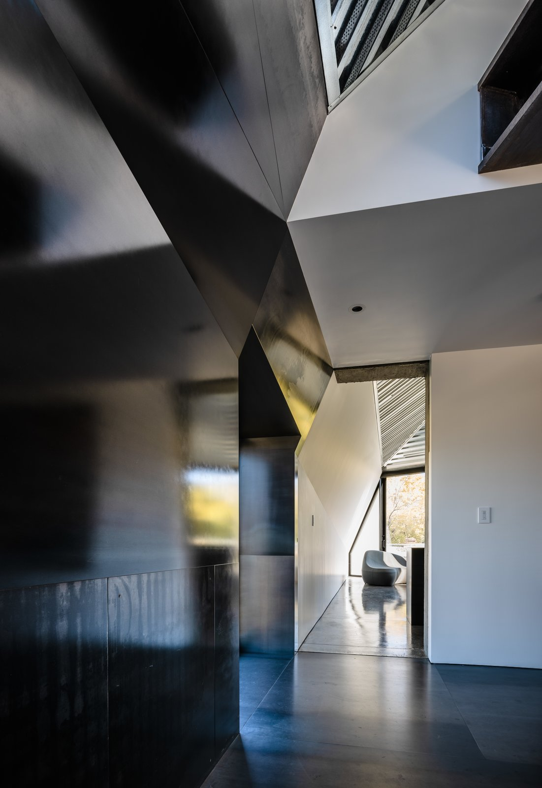 Hallway and Concrete Floor Contrasting materials, like blackened steel, silvery zinc, and white sheetrock, converge at odd angles.  Photo 15 of 19 in Two Art World Veterans Live in This Mind-Bending Metal Home in Nevada