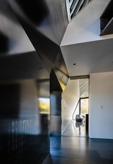 Contrasting materials, like blackened steel, silvery zinc, and white sheetrock, converge at odd angles.