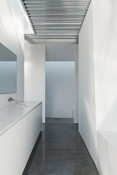 Concrete Floor In the master bath, a Boffi tap pairs with a Kohler sink.  Photo 12 of 19 in Two Art World Veterans Live in This Mind-Bending Metal Home in Nevada