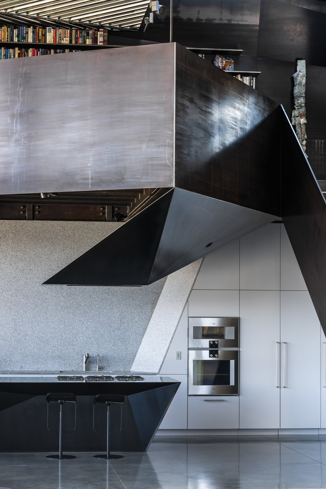 Kitchen, White Cabinet, Undermount Sink, Wall Oven, and Concrete Floor The kitchen features appliances by Gaggenau, a faucet by KWC, and barstools by Shin and Tomoko Azumi.  Photo 13 of 19 in Two Art World Veterans Live in This Mind-Bending Metal Home in Nevada