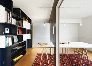 A movable wall clad in wainscoting on one side slides along tracks in the dining room ceiling, dividing the room into a meeting space and a library. The Shiro Simple Modern Pendant lights can be easily removed and reattached after moving the wall.