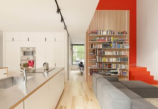 The open-plan kitchen and living room in the de Gaspé House in Montreal's Villeray neighborhood borrows natural light from a double-height space over the seating area, augmented by the colorful staircase framing the bookshelves.