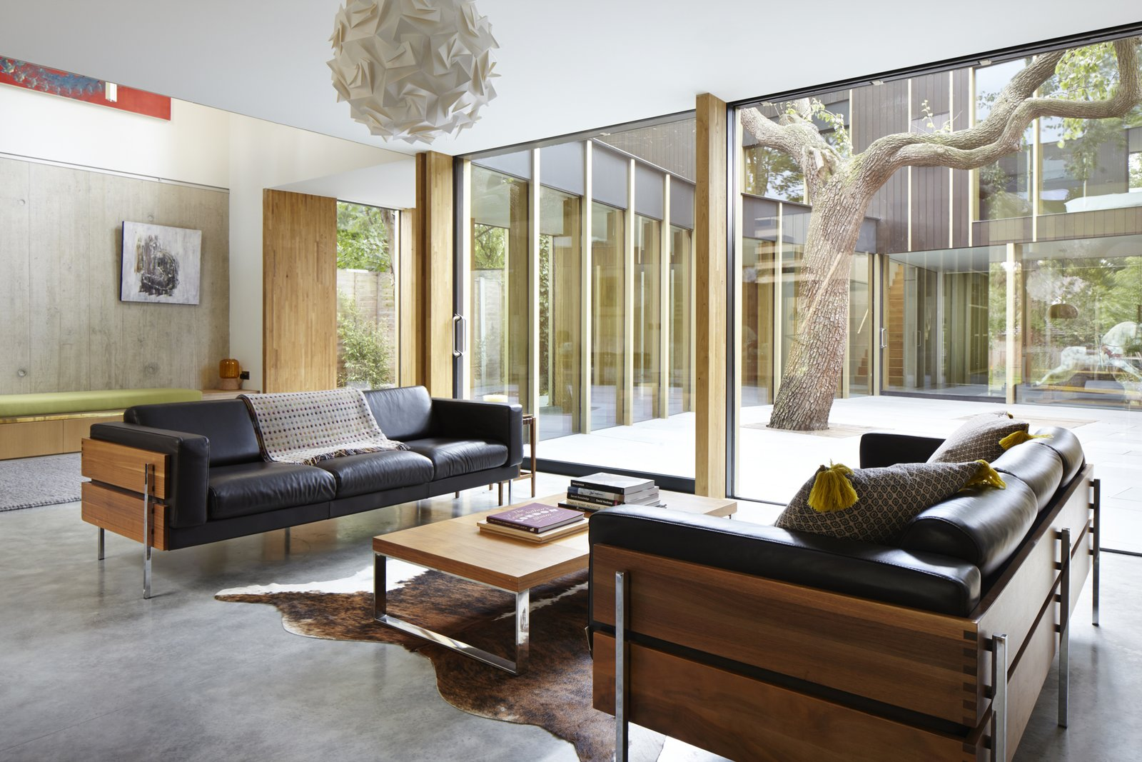 Living Room, Sofa, Concrete Floor, Coffee Tables, and Pendant Lighting The sofas are designed by Robin Day for Habitat. The walnut frame nicely contrasts with the soft leather cushions.  Photo 5 of 9 in This Modern Courtyard Home Celebrates a 100-Year-Old Tree