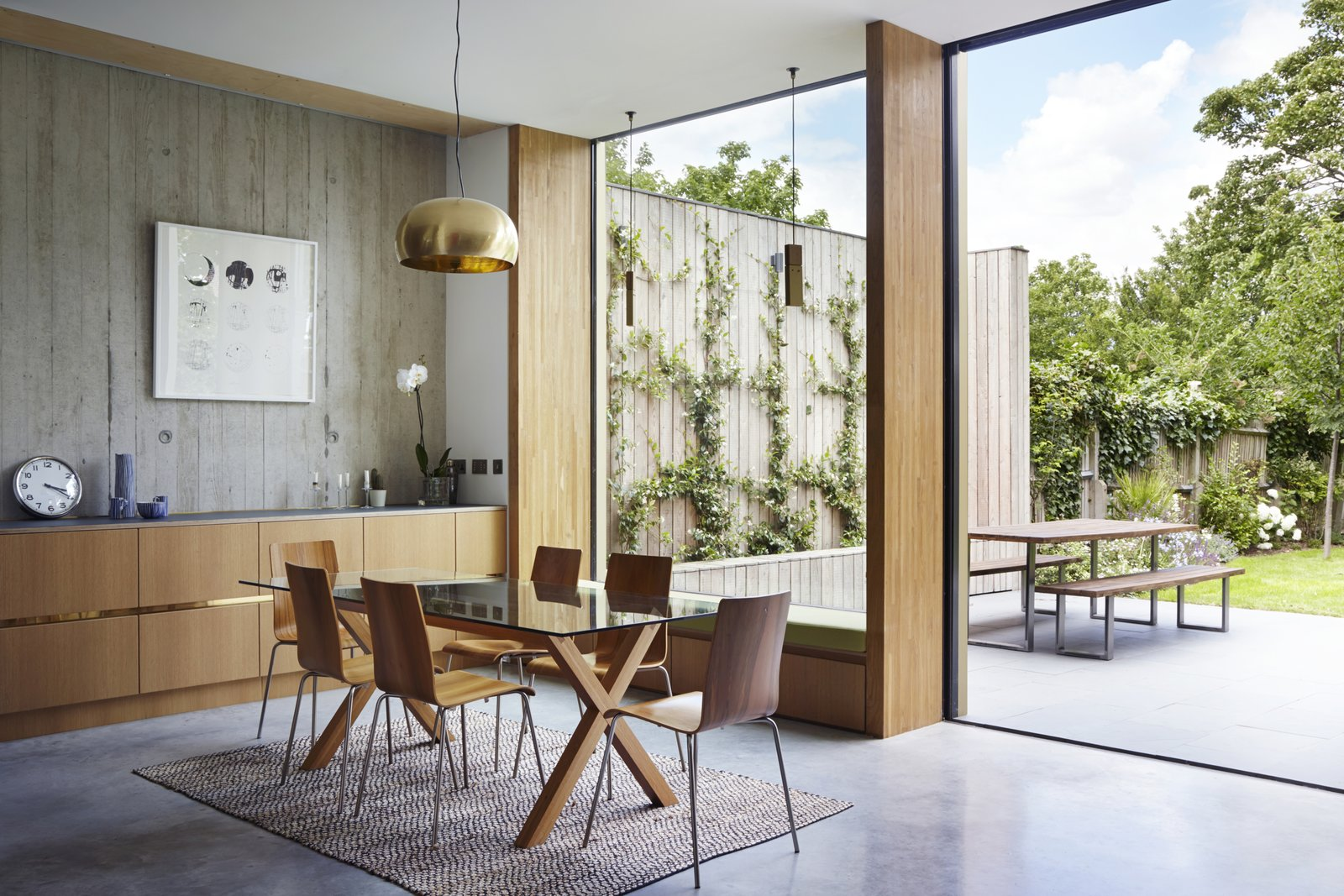 Dining Room, Table, Chair, Concrete Floor, Pendant Lighting, Rug Floor, and Storage The dining room table is also from Habitat. The oak veneered plywood is from Peter Benson Plywood.  Photo 7 of 9 in This Modern Courtyard Home Celebrates a 100-Year-Old Tree