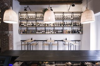 Shown here is a frontal view of the Studio DiDeA-designed bar stools and tables that are connected to a sliding track system. Above these furnishings, modular shelves feature a selection of wines available for sale.