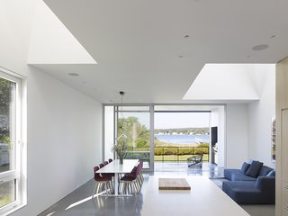The Quonochontaug House in coastal Rhode Island is located three hours from New York City and is built as a retreat for a family from Brooklyn. The design is organized around an open-plan ground floor punctuated by a series of double-height sky-lit spaces that progress from entry to bay view.