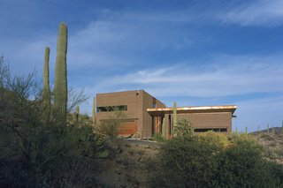 Three pavilions of masonry, rusted steel, and glass come together in Tucson, Arizona, to create a home designed by Ibarra Rosano Design Architects that draws inspiration from the desert landscape. Each facade is in direct response to the sun, wind, topography, vegetation, and views. Windows are long and shaded, entryways are covered, and views are curated to capture indirect sunlight and provide vistas of the landscape beyond.