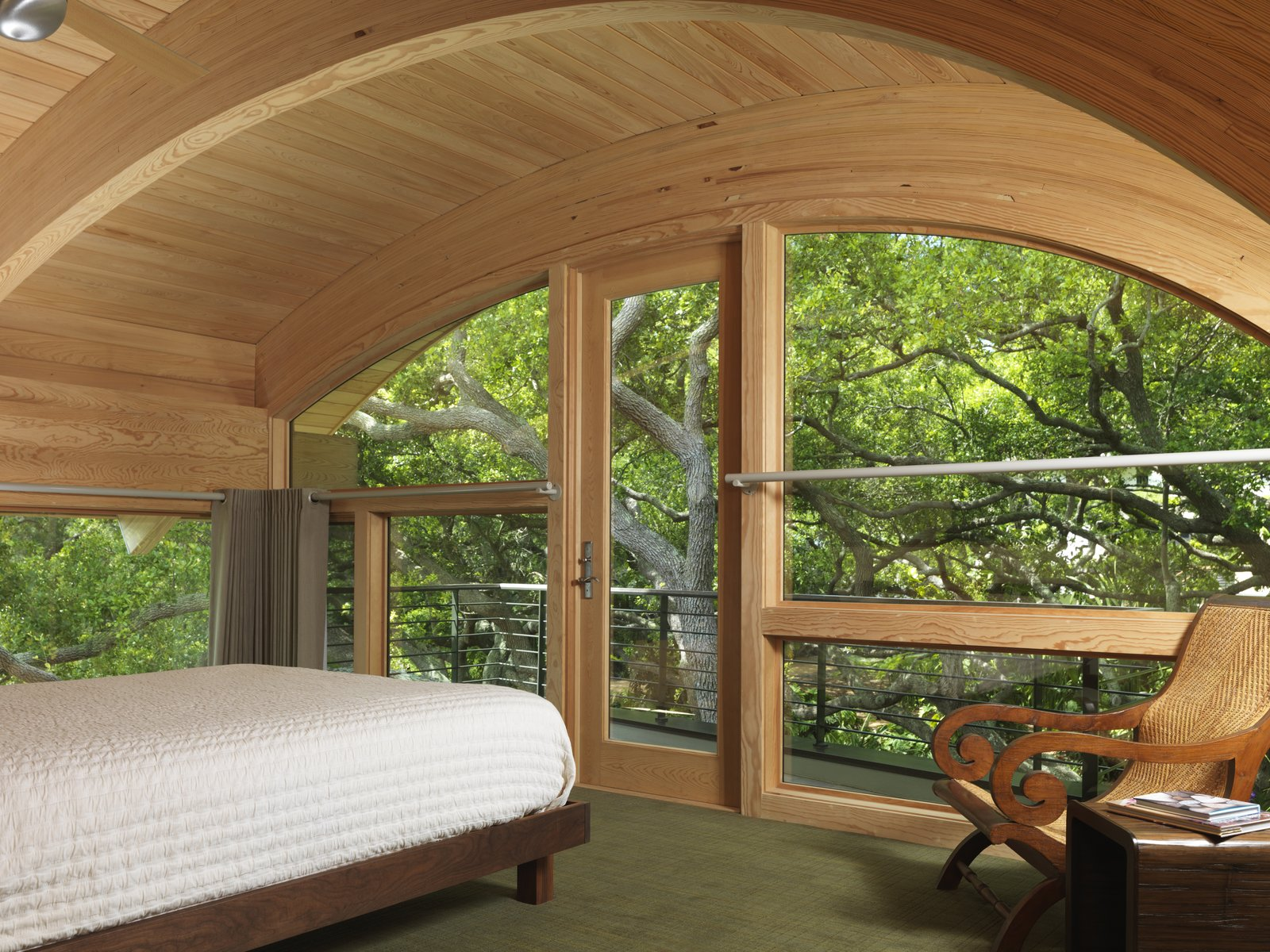 Casey Key House  In this playful treehouse-style bedroom, custom arched windows surround the room and meet the wooden ceiling. Elements of wood and modern architecture draw the sound of rustling leaves and midday breeze into this cozy treetop retreat.  Architect: Jerry Sparkman; Architecture Firm: Sweet Sparkman Architects; Location: Casey Key, FL   #marvin #windows #doors  #indoor #outdoor #transition #caseykeys #FL    Photo 18 of 25 in Photo Essay: Enchanting Tree Houses