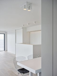 Knokke is a minimal space created by Belgium-based designers minus. The space is characterized by a wrap-around balcony that overlooks the ocean. Panoramic windows span both walls of the main living area to take advantage of the view as well. Both the kitchen and entertainment unit are concealed by a series of sliding doors. An array of cubic spot lighting provides additional illumination for areas such as the kitchen counters, dining table, and sofa.