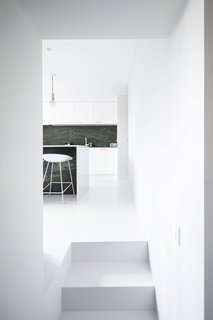 Niels & Annemie is a minimal residence located in Brussels, Belgium, designed by Benoît Deneufbourg and la fabrika studio. The design brief was clear; Niels and Annemie wanted to keep the classical 'Hausmann grandeur' (high ceilings, large rooms, white walls, wooden floors) and combine this with modern lines and materials. The design approach was to keep it simple by using a black and white color scheme as the basis throughout the apartment. Their collection of Scandinavian and Italian furniture mixed with some original vintage pieces complements this refined interior, effortlessly blending old and new.