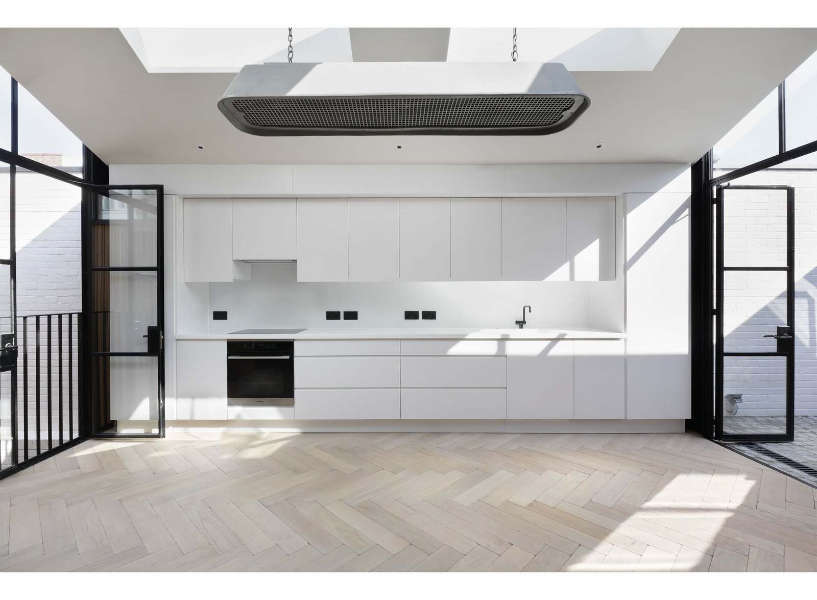 Kitchen, Wall Oven, Cooktops, Drop In Sink, Light Hardwood Floor, White Cabinet, and Recessed Lighting  Best Photos from The Courtyard House