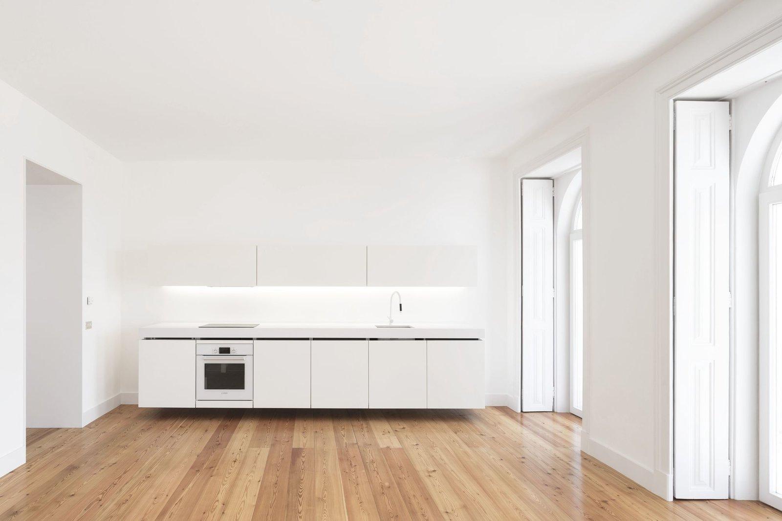 Kitchen, Granite Counter, White Cabinet, Medium Hardwood Floor, and Range  Tap Building