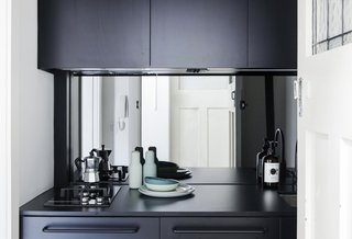 In a compact apartment in Australia, the kitchenette uses a mirrored take on the glass backsplash to bring in an element that would reflect light (and views). The mirrored backsplash is relatively easy to clean with the right cleaning tools, but might drive a clean freak a little crazy. Regardless, it's a great contrast to the dark cabinets.