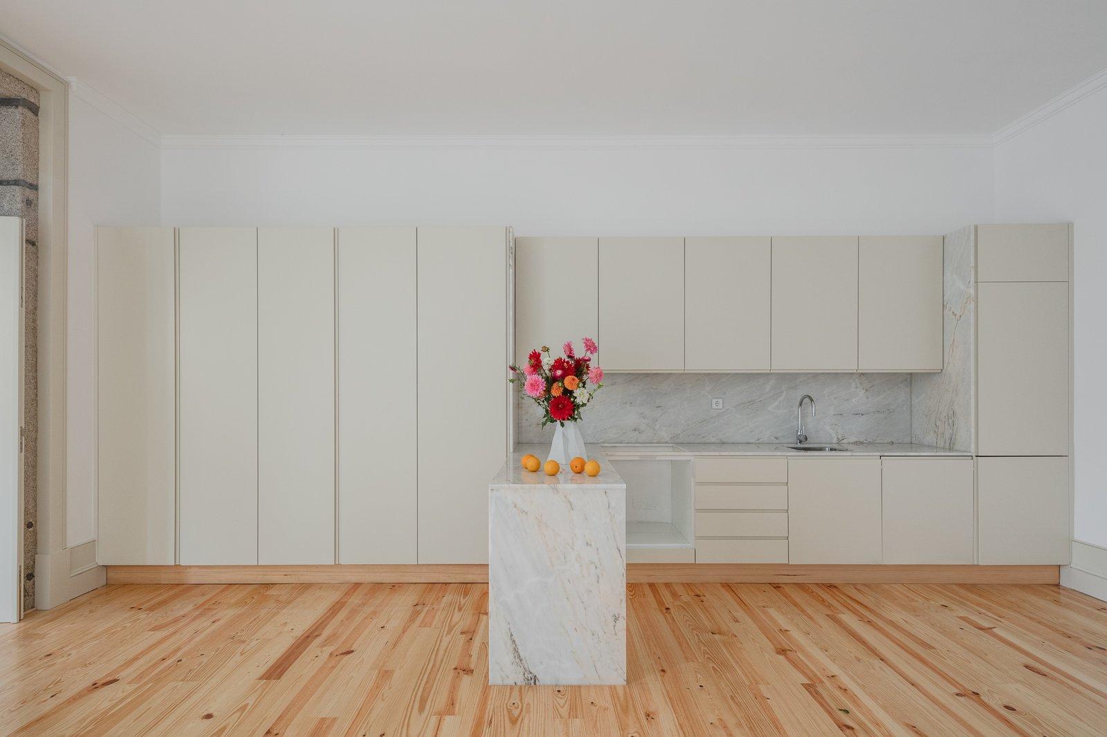 Kitchen, Marble Counter, White Cabinet, and Light Hardwood Floor  Rua da Boavista