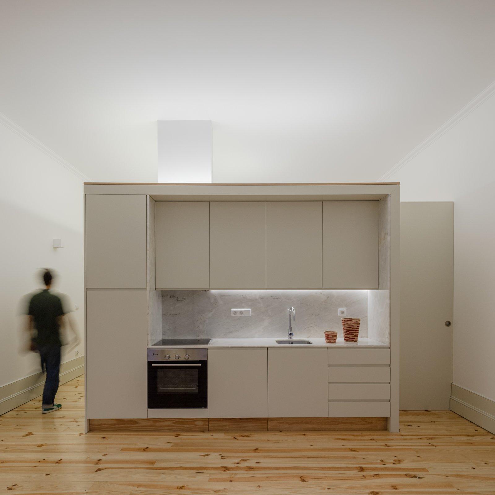 Kitchen, Light Hardwood Floor, White Cabinet, Marble Counter, and Marble Backsplashe  Rua da Boavista