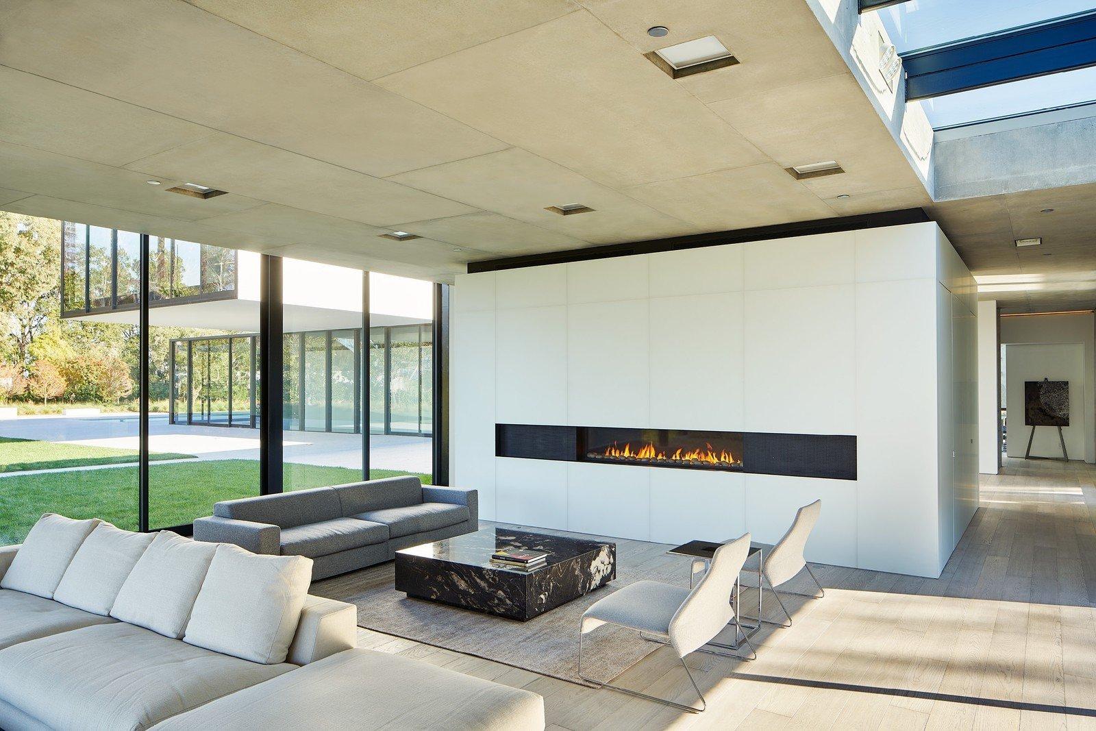 Tagged: Living Room, Gas Burning Fireplace, Ceiling Lighting, Sofa, and Light Hardwood Floor.  OZ Residence