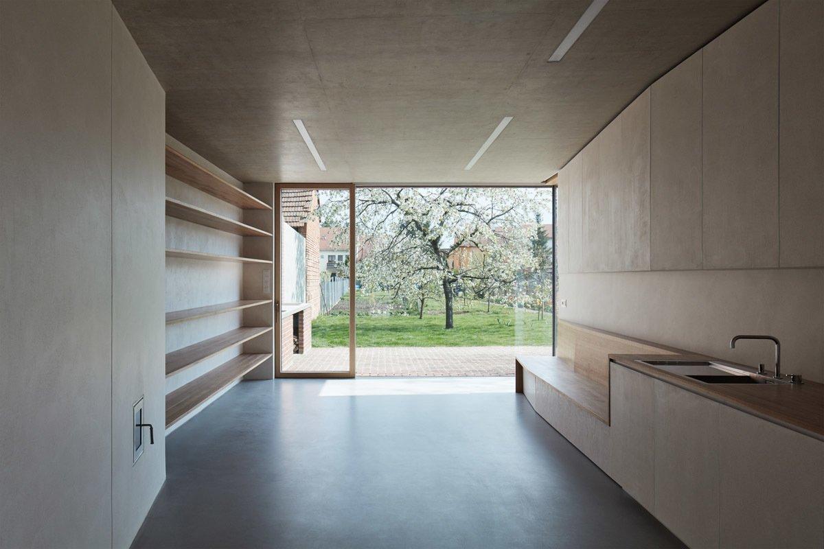 Kitchen, Wood Counter, Concrete Floor, Recessed Lighting, Concrete Backsplashe, and Undermount Sink  Brick Garden with Brick House