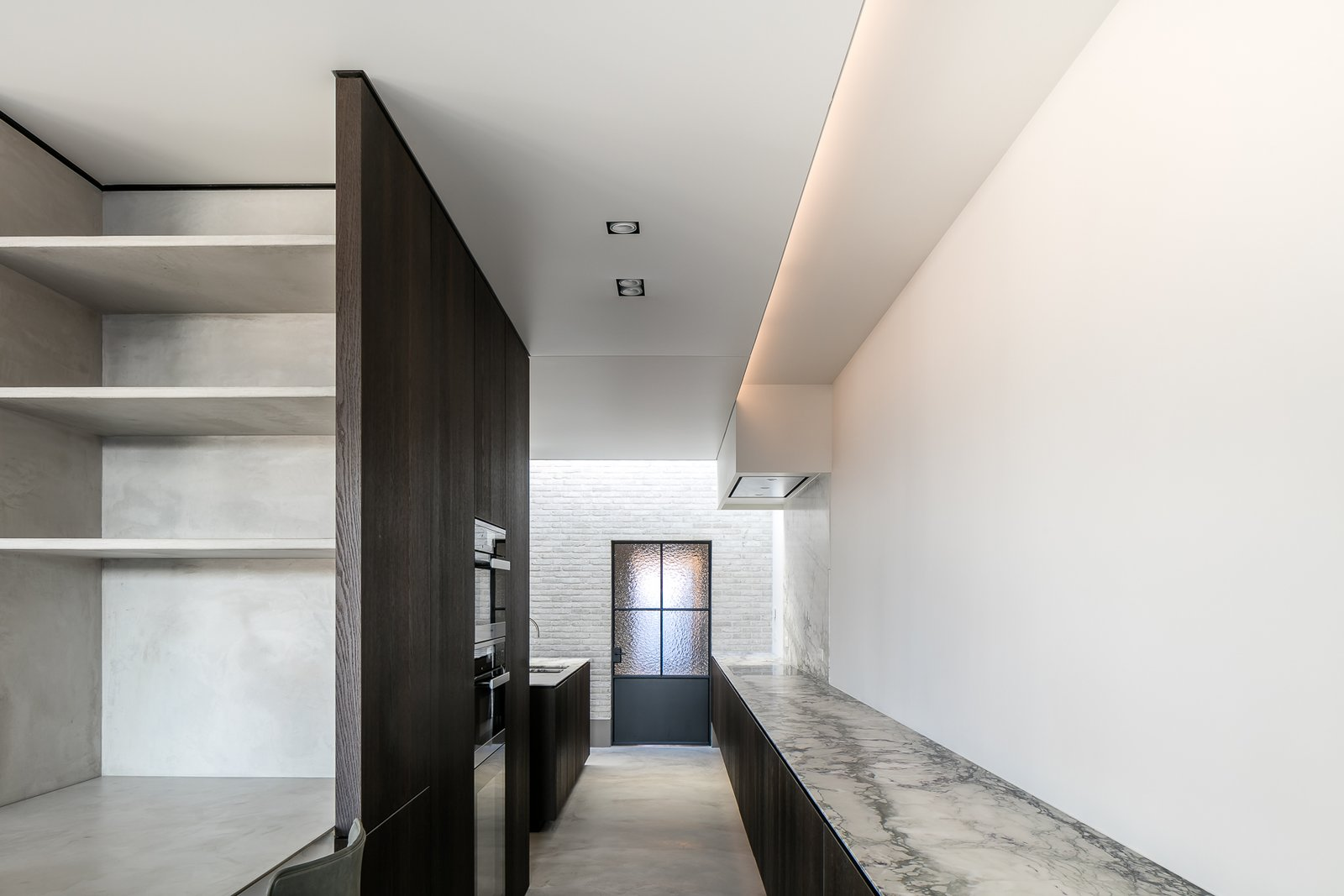 Kitchen, Marble Counter, Light Hardwood Floor, Ceiling Lighting, and Wall Oven  Circu House