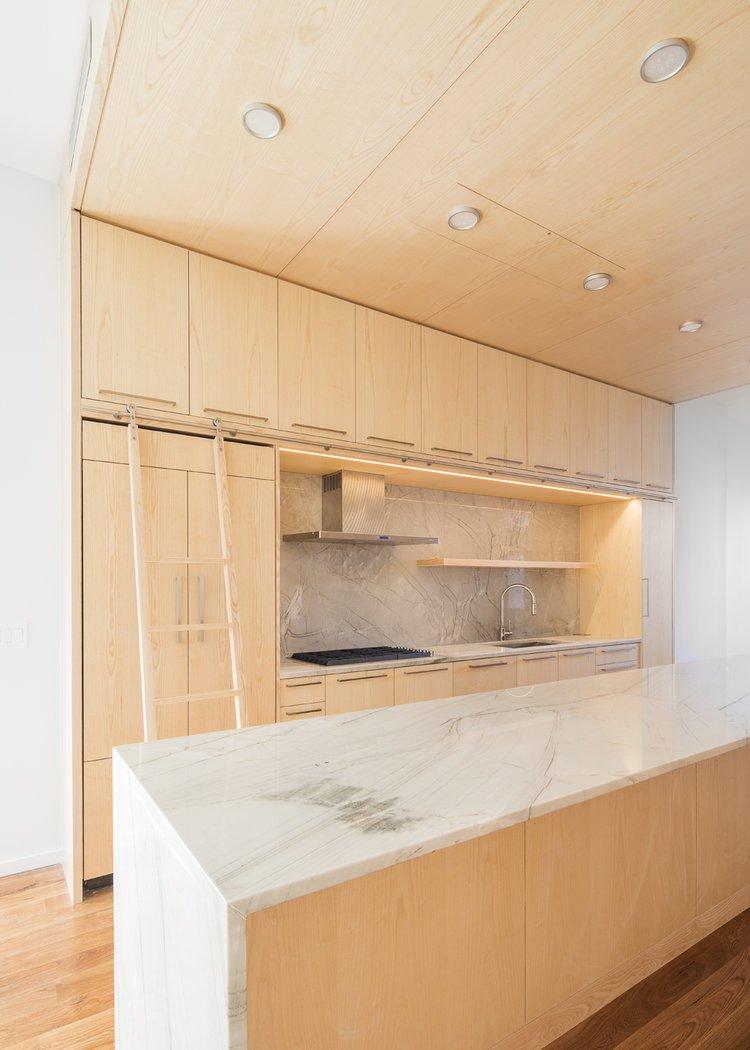 Kitchen, Wood Cabinet, Light Hardwood Floor, Marble Backsplashe, Marble Counter, Recessed Lighting, Range, Range Hood, and Undermount Sink  Wayne Street Row House