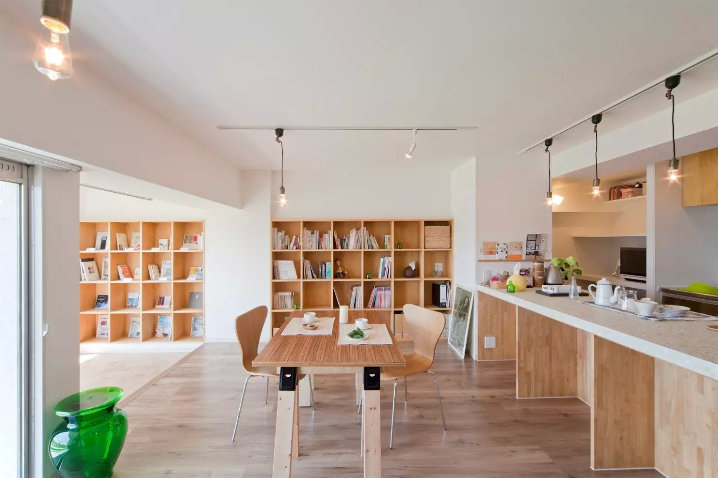 Living Room, Chair, Track Lighting, Medium Hardwood Floor, and Bookcase  Book Cafe House