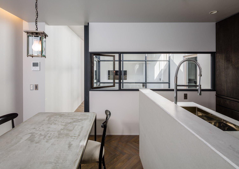 Kitchen, Marble Counter, Medium Hardwood Floor, Pendant Lighting, and Undermount Sink  Residence in Takariya