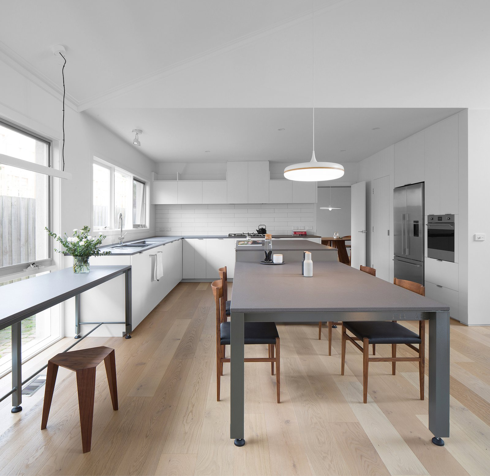 Kitchen, Subway Tile Backsplashe, White Cabinet, Light Hardwood Floor, Granite Counter, Pendant Lighting, Refrigerator, Undermount Sink, Wall Oven, and Range  Corhampton Rd Residence