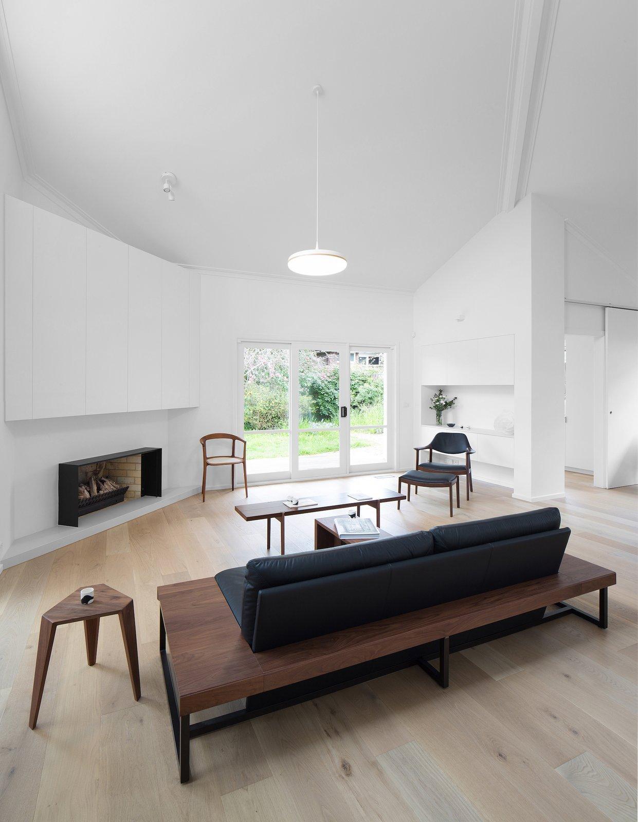 Living Room, Pendant Lighting, Chair, Coffee Tables, Bench, Wood Burning Fireplace, and Light Hardwood Floor  Corhampton Rd Residence