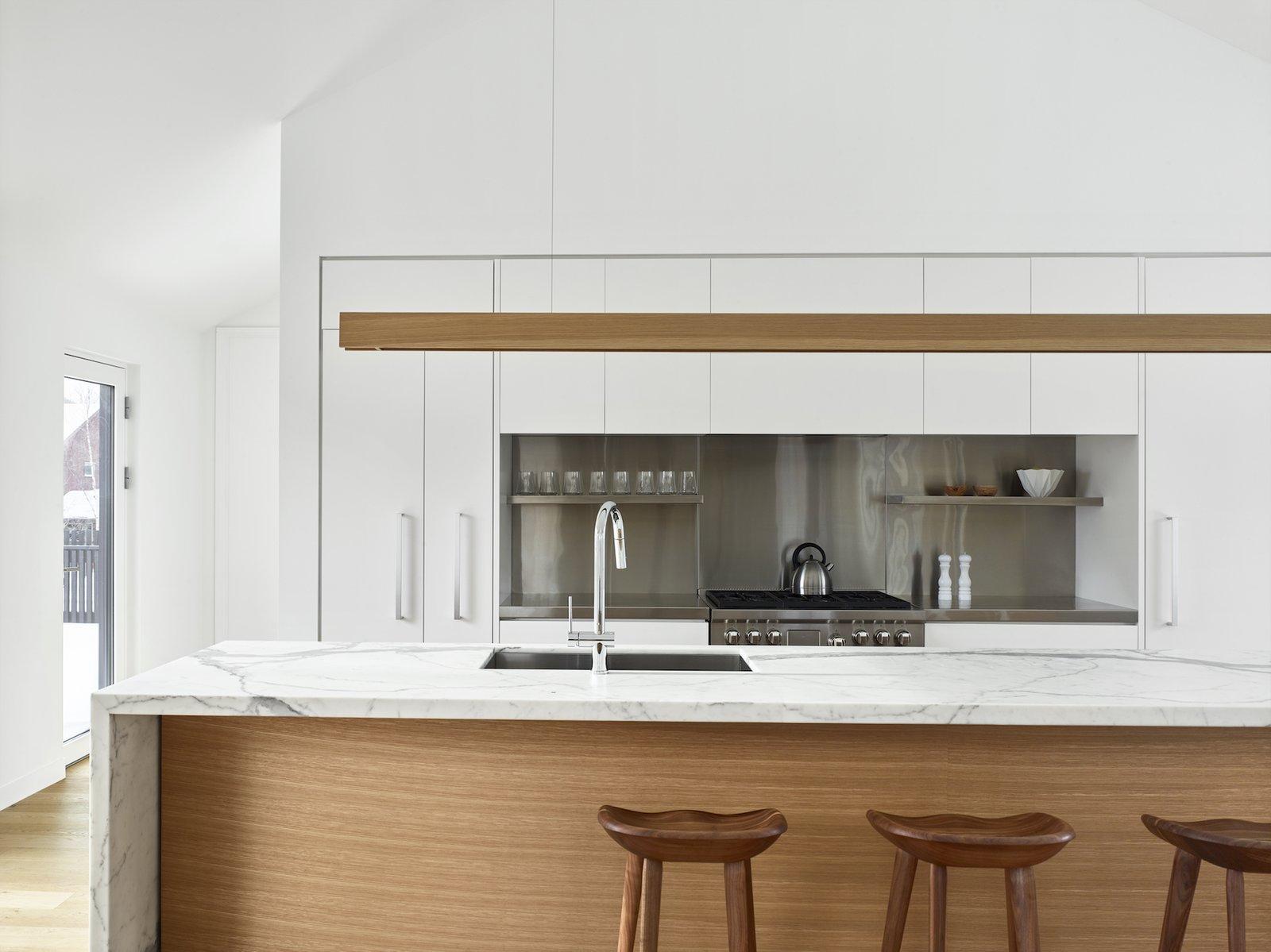 Kitchen, Marble Counter, Light Hardwood Floor, Track Lighting, Range, White Cabinet, Metal Backsplashe, and Undermount Sink  Alta Chalet