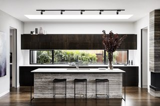 In this kitchen in Australia, a freestanding island is lit by a skylight and track lighting, while the texture and color of the siding of the island provide a marked contrast to the dark cabinetry of the rest of the kitchen. An oversized sink makes the island an ideal prep space.