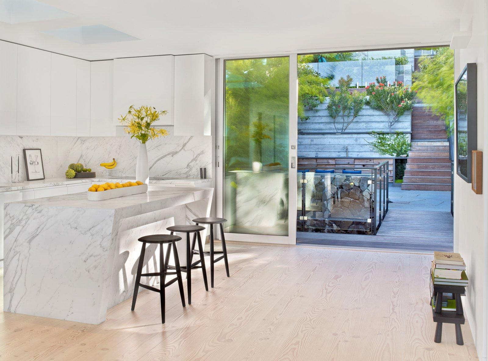 Kitchen, Marble Counter, White Cabinet, Light Hardwood Floor, Marble Backsplashe, and Ceiling Lighting  Glen Park Residence by CCS ARCHITECTURE