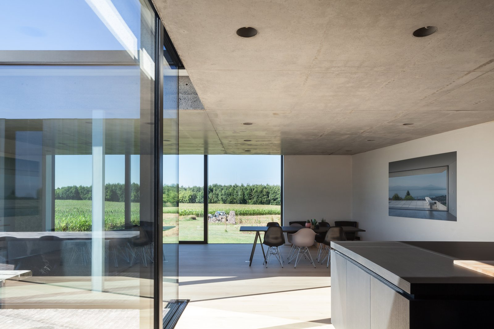 Dining Room, Table, Recessed Lighting, Chair, and Light Hardwood Floor  Photo 6 of 14 in Defying traditionalism: concrete bungalow inserted in a rural Belgian landscape
