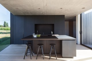 The building materials, have been guided by the vibrant colours of the rural landscape. Grey wood, patterned concrete and dark, anodised windows are the main components. The use of concrete is a wink to the historical nature of the surroundings and accentuates the massiveness of the building. Oak floors provide warmth to the interior and the kitchen area made of black-stained oak acts as a resting point. These basic colours make sure the focus is on what is happening outside, not inside.