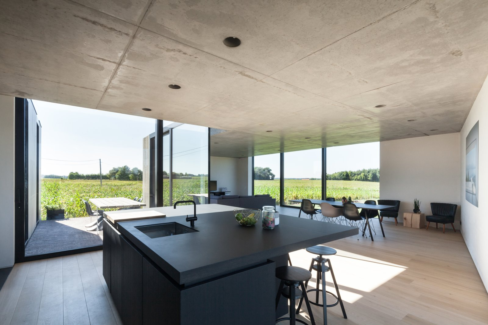 Dining, Chair, Bar, Stools, Light Hardwood, Table, and Recessed  Best Dining Table Recessed Stools Light Hardwood Photos from Defying traditionalism: concrete bungalow inserted in a rural Belgian landscape