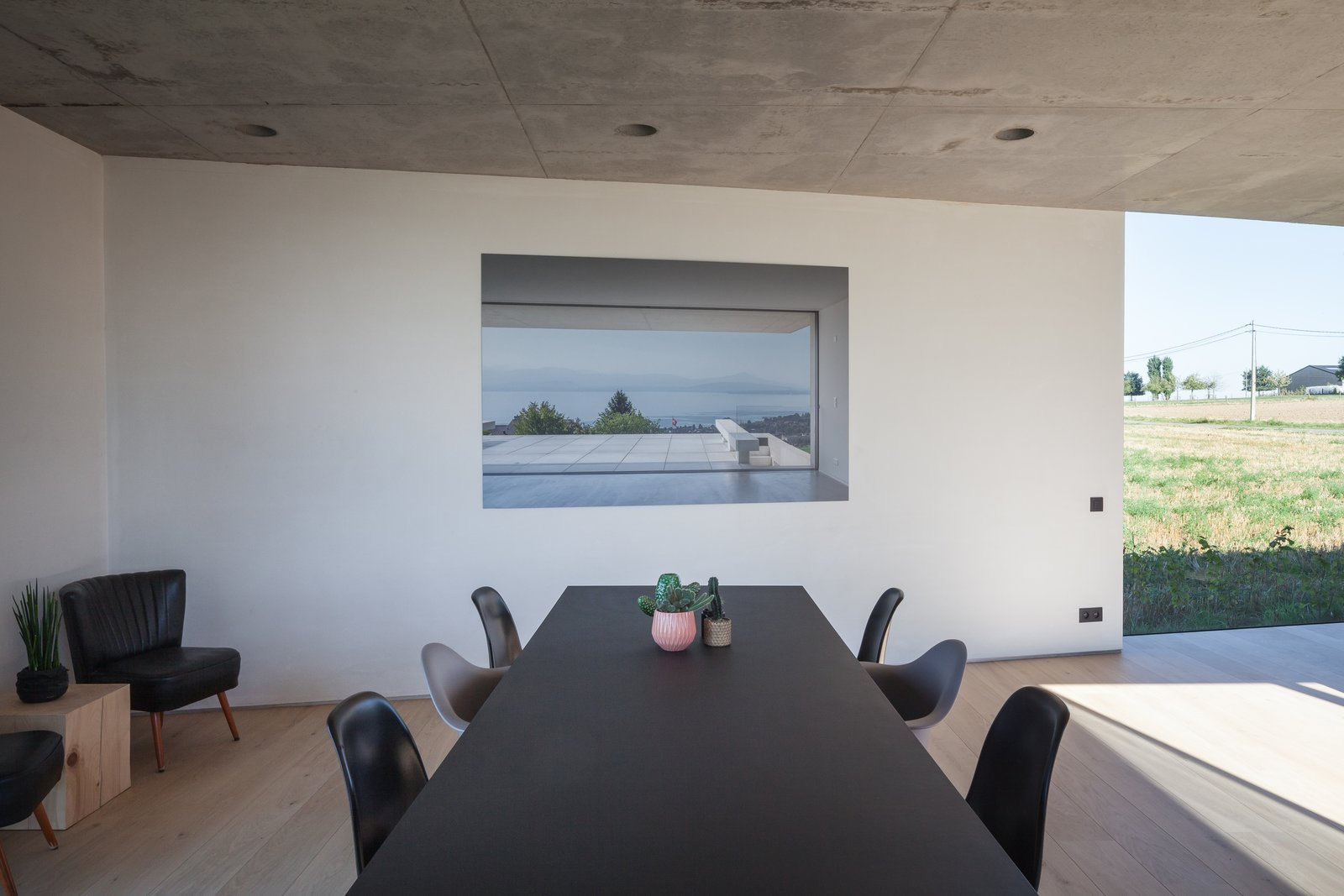 Dining Room, Chair, Recessed Lighting, Light Hardwood Floor, and Table  Photo 10 of 14 in Defying traditionalism: concrete bungalow inserted in a rural Belgian landscape