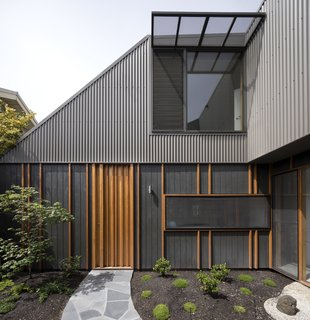 Although the property looks like a one-story home from the street, its second level is more noticeable from the enclosed courtyard. Blackbutt vertical battens provide texture to shadowclad exterior plywood with an Onyx Quantum Aquaoil finish.