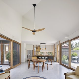 Blackbutt window treatments and a polished-concrete floor unify the kitchen, dining, and living areas on one end of the courtyard. A Haiku ceiling fan by Big Ass Fans provides extra air.