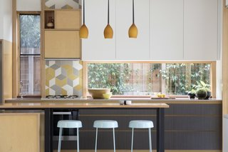 "Gewinn pendant lights match the woodwork in the kitchen. Urban Edge's Mutina ""Tex"" Splashback tiles add a graphic element against Flexipanel cupboard doors painted in ""Parchment Matte."""