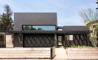"Benjamin Moore's ""Universal Black"" distinguishes the exterior from the unfinished spruce fence."