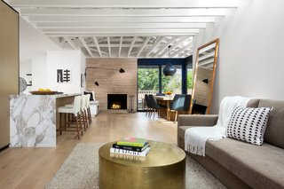 Custom white oak by Contempo Floor Coverings spreads across the floor in the open living area.  Malibu Market and Design supplied the metal coffee table, and the rug was purchased from Restoration Hardware.