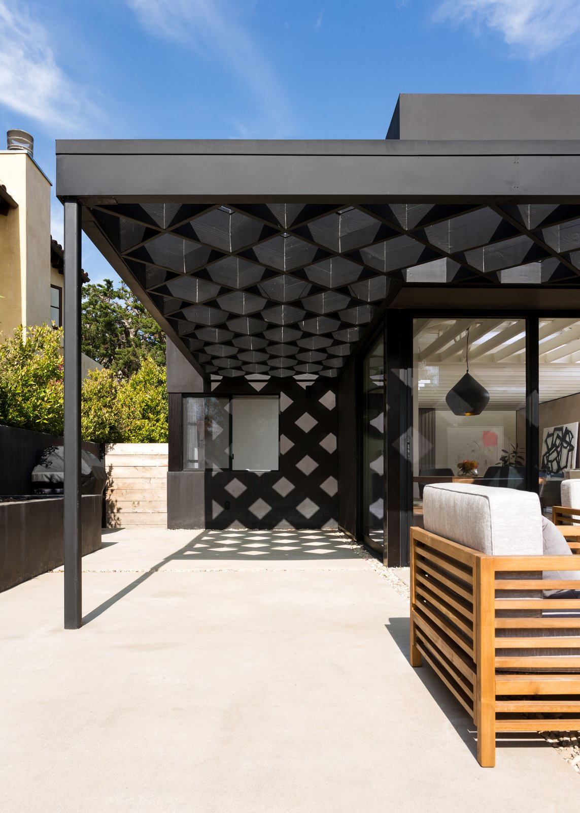 Outdoor, Back Yard, and Concrete Patio, Porch, Deck A steel and redwood fabrication makes up the diamond shape of the trellis.  Photo 11 of 12 in The Woman Who Grew Up in This L.A. Home Returned to Give it a Stunning Renovation