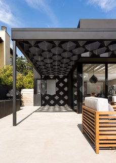 A steel-and-redwood fabrication makes up the diamond shape of the trellis.