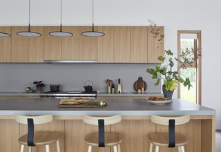 Caesarstone countertops are used in the kitchen. Skan pendants by Vibia hang above the island.