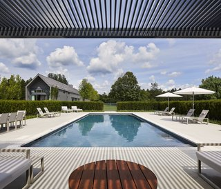 """This Modern Farmhouse Outside Toronto Makes Its Own Rules - Photo 9 of 11 - """"It's a big property, so we had space to spread out,"""" he says. """"The pool is purposefully removed from the main house in order to make it feel like a destination."""" Ninix by Royal Botania furniture sits under Tucci umbrellas."""