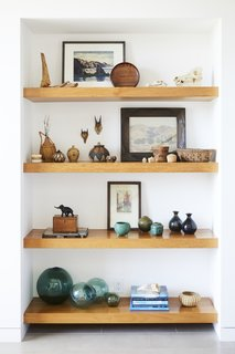 Teak shelves were used in the entryway to display the owners' art collection and souvenirs from abroad.