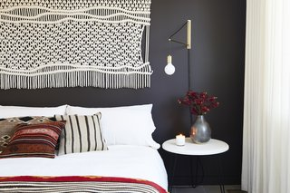 In the second bedroom, a macrame wall hanging and gold sconce were found at Etsy, which matches the sentiment of the DIY nightstand. Matteo bedding pops against the Midsummer Night wall color by Benjamin Moore.