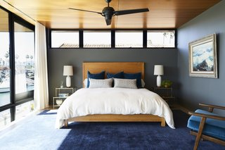 The master bedroom unites the rest of the home's shades and textures in a calm palette. The custom bed is centered above a Crate and Barrel area rug. As with most of the art in the home, the one hanging above on the right is from the owners' personal collection.