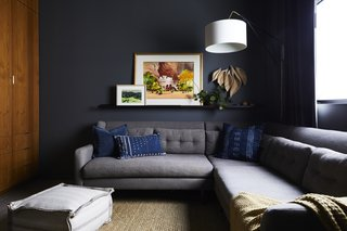 In the den, the Kendall Charcoal paint shade by Benjamin Moore is matched by the equally dark shade of the West Elm sofa. Artist Laura Buchan supplied the wooden sculpture, and the floor pouf was sourced from Porch in nearby Carpinteria.