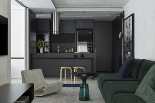 Since the owner wanted as much of an open concept as possible, Revollo used a small but impactful detail to designate each space: color. For instance, the kitchen is defined by black, the living area by gray, and the dining space by honey. Joinery Inovart created the L-shaped dining table connected to the kitchen counter.